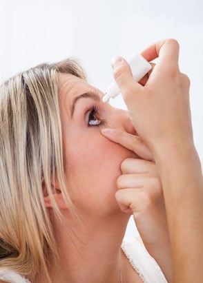 image of a woman using eye drops